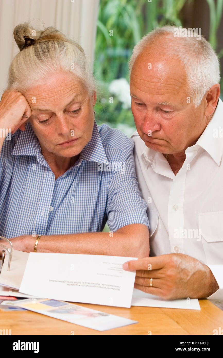 Elderly married couple reading pension award - Stock Image