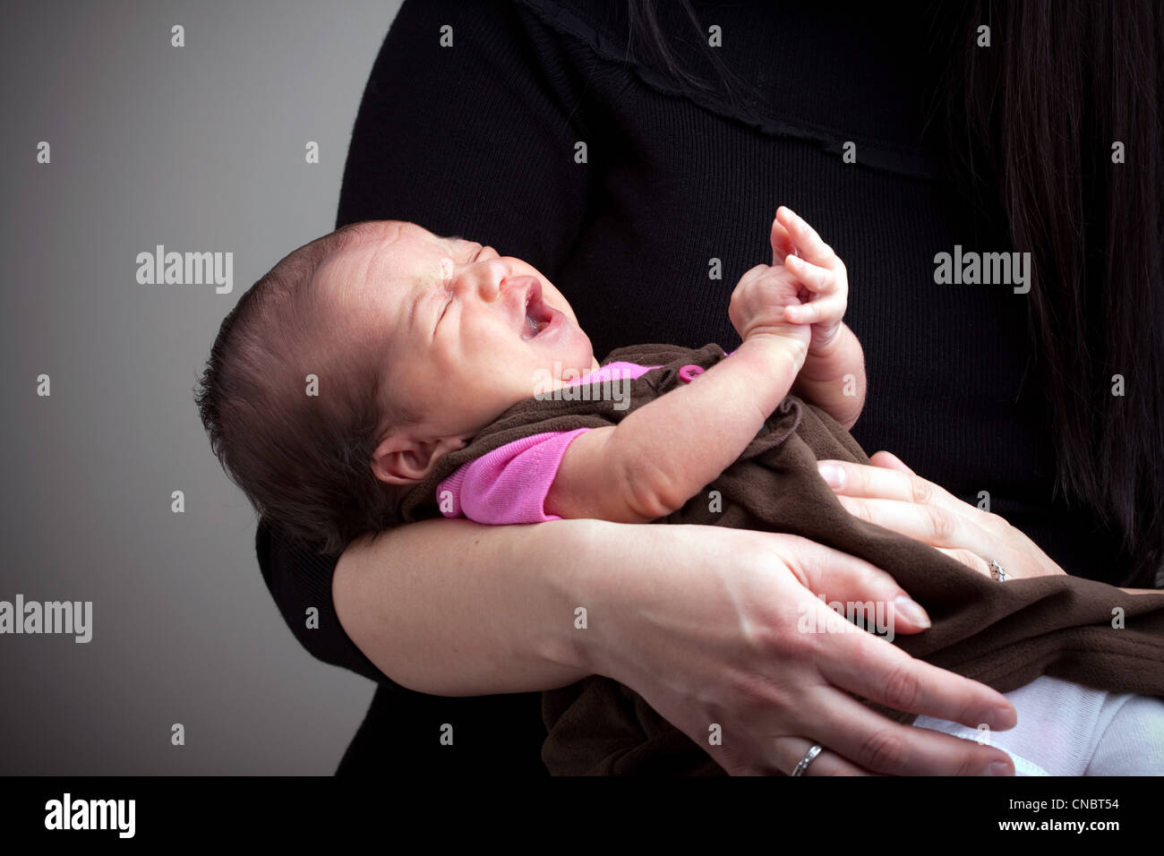 A mom holds a young newborn baby girl in her arms that is upset and crying. - Stock Image
