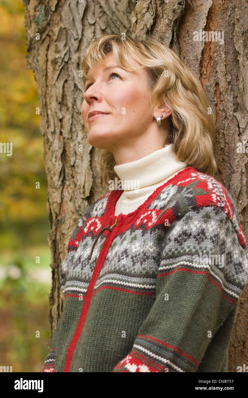 Woman leaning against a tree - Stock Image