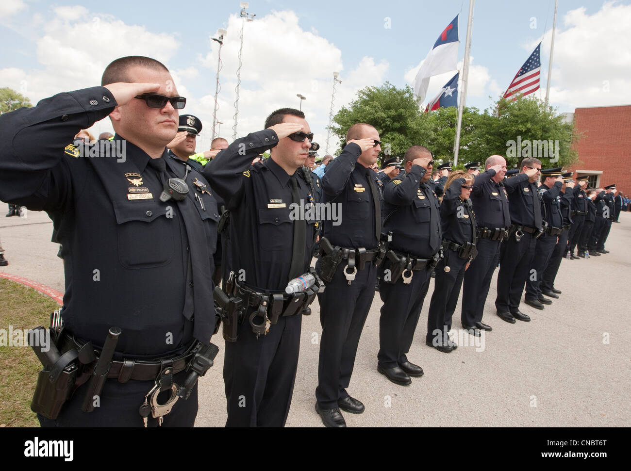 Officers salute during funeral for Austin Police Officer Jaime Padron, who was killed in the line of duty in a full Stock Photo
