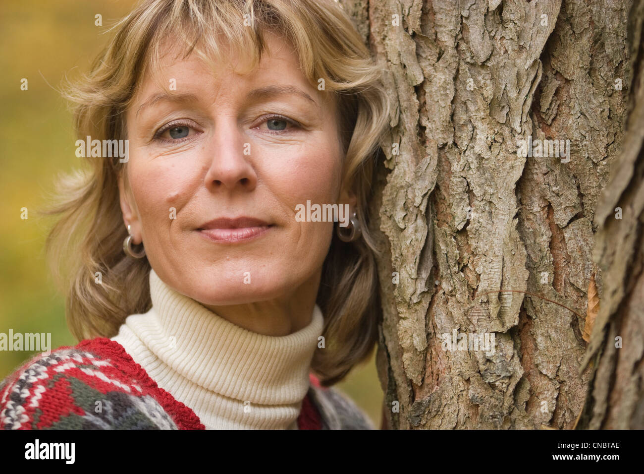 Portrait of a woman leaning against a tree - Stock Image