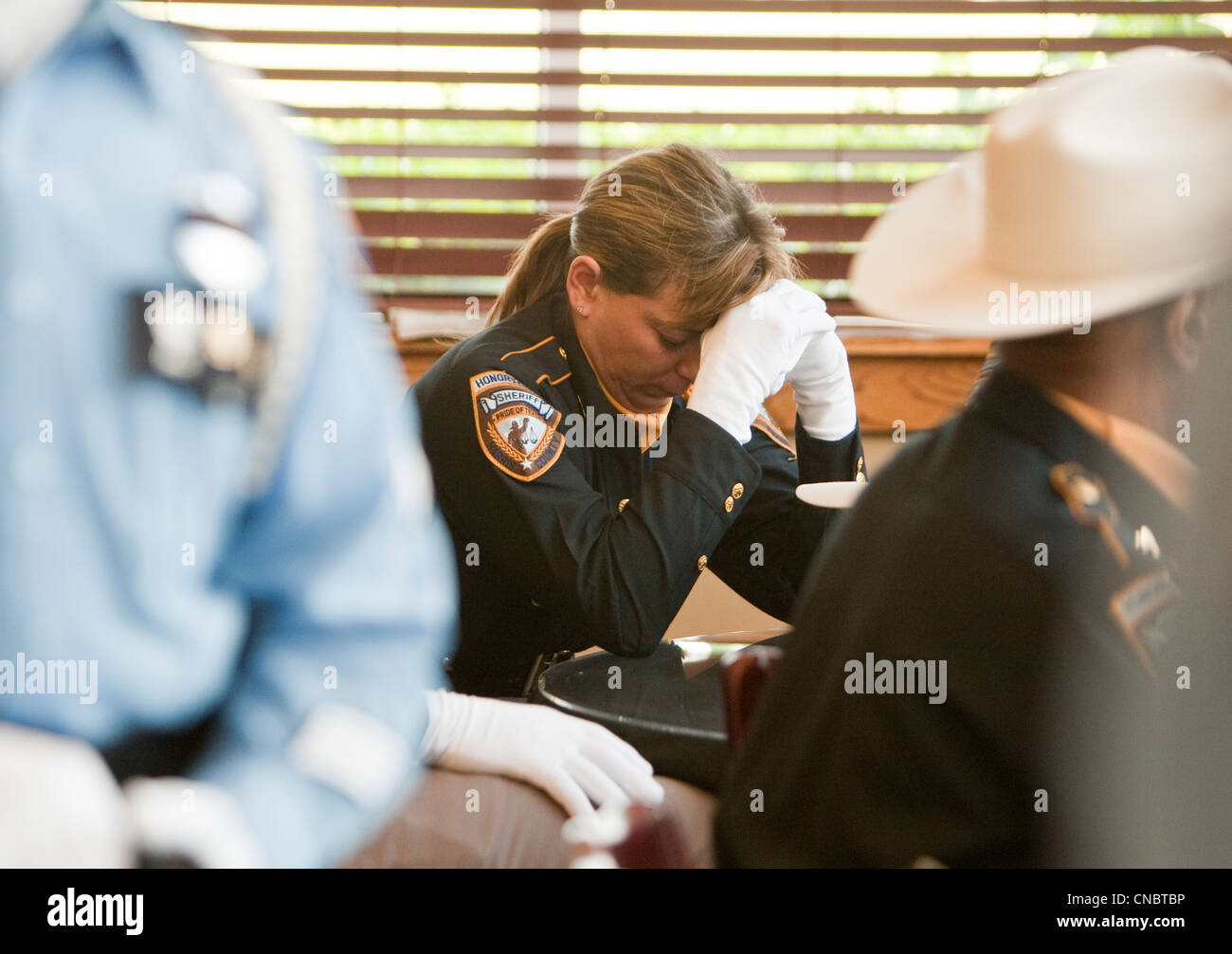 female reflects during funeral for Austin Police Officer Jaime Padron, who was killed in the line of duty in a full - Stock Image