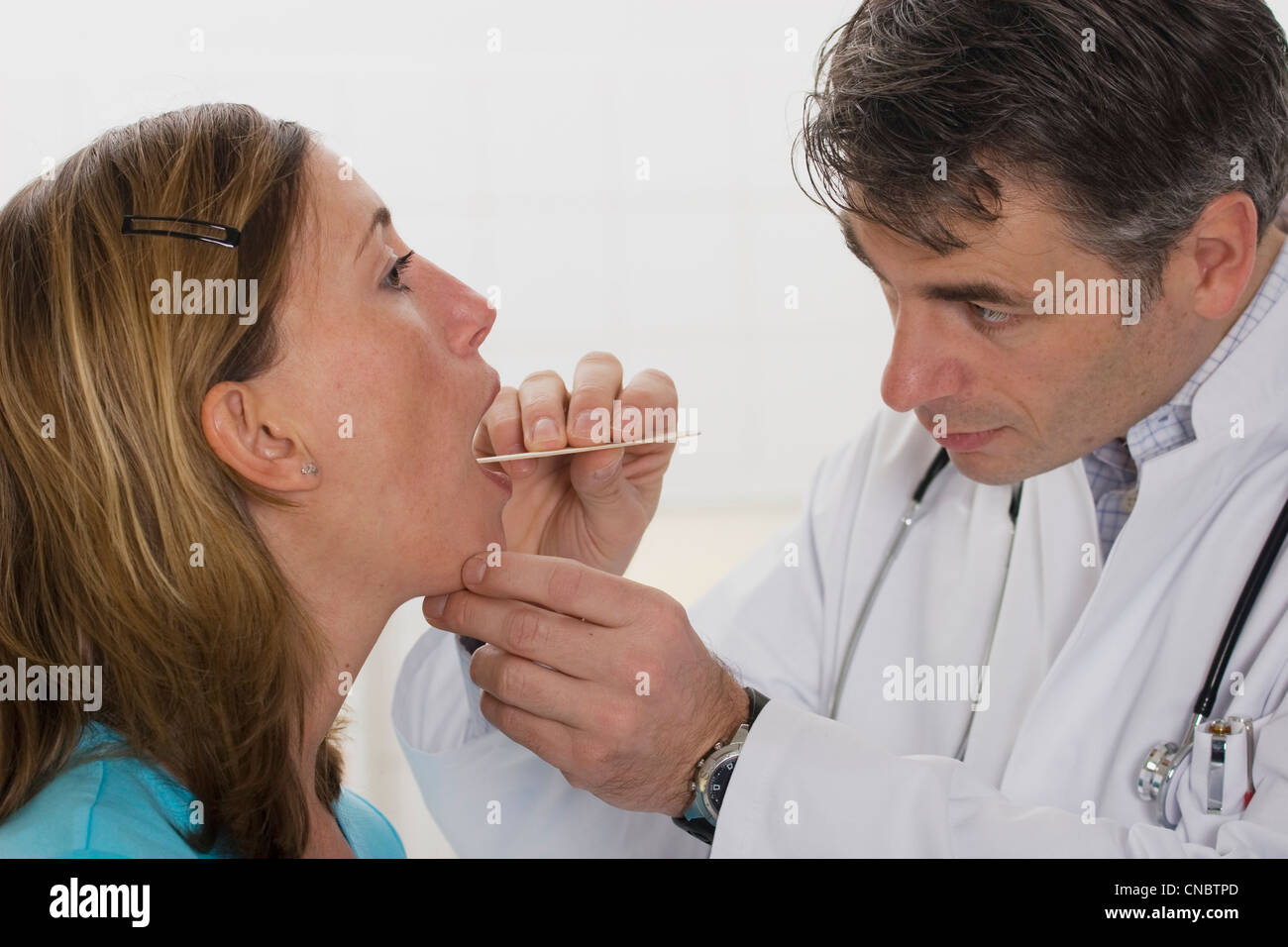 ENT physician examining pharynx of a female outpatient - Stock Image