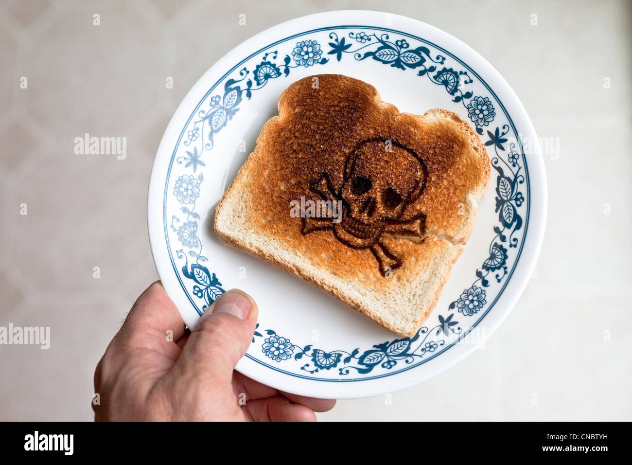skull and crossed bones burned into a piece of toast on a plate. celiac disease Gluten Allergy - Stock Image