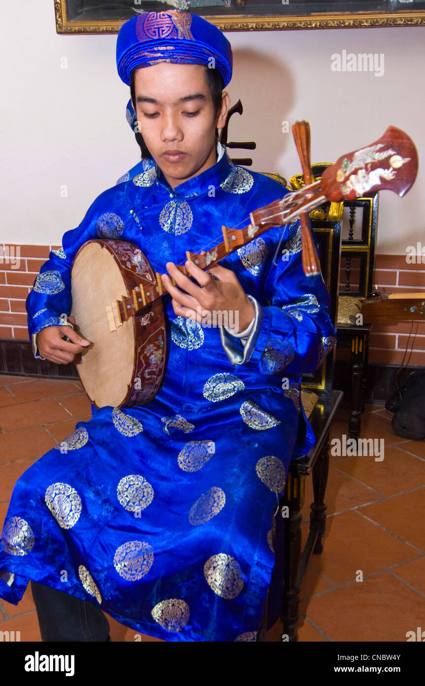 Vertical close up view of traditional Vietnamese musician playing the dan nguyet or Full Moon lute guitar in costume. - Stock Image