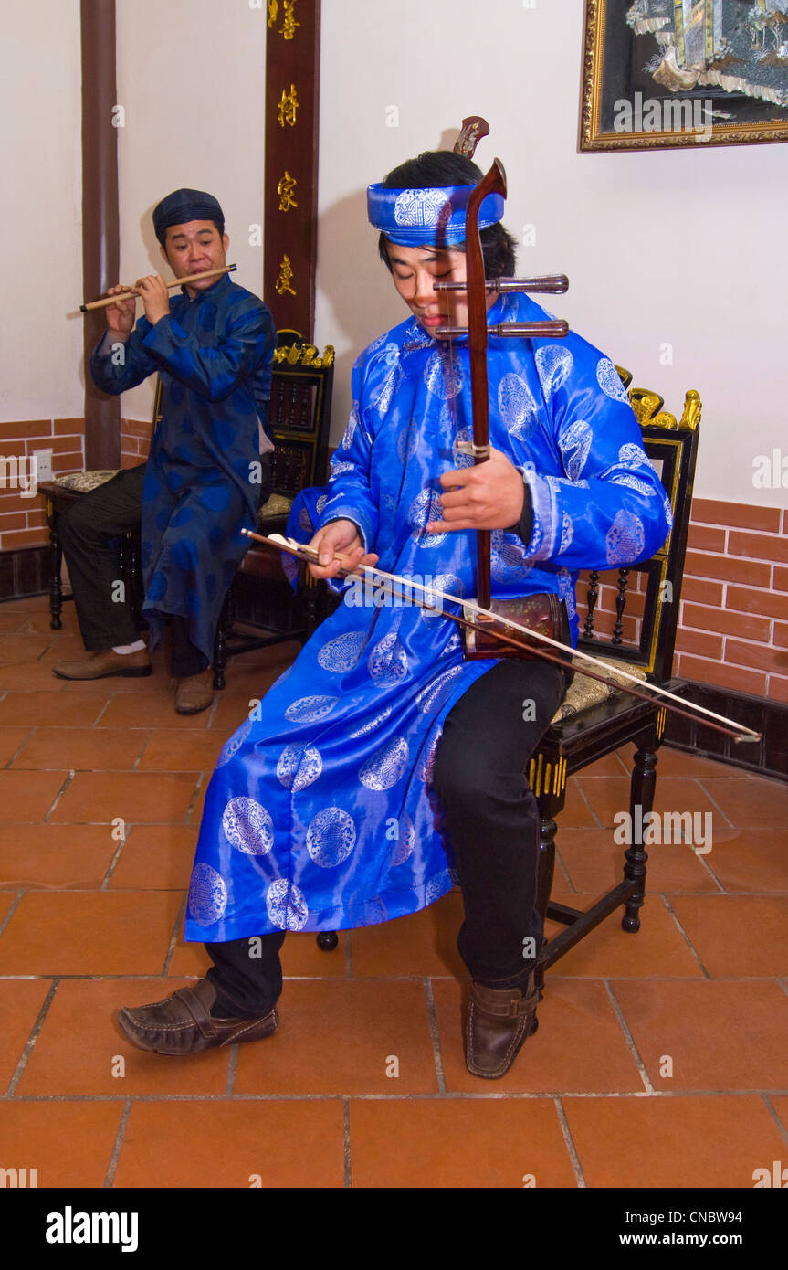 Vertical close up view of traditional Vietnamese musician playing the dan nhi or vertical violin in bright coloured Stock Photo