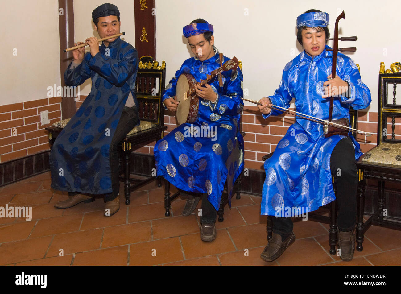 Horizontal view of a traditional Vietnamese musicians playing and singing traditional folklore songs in costume. - Stock Image