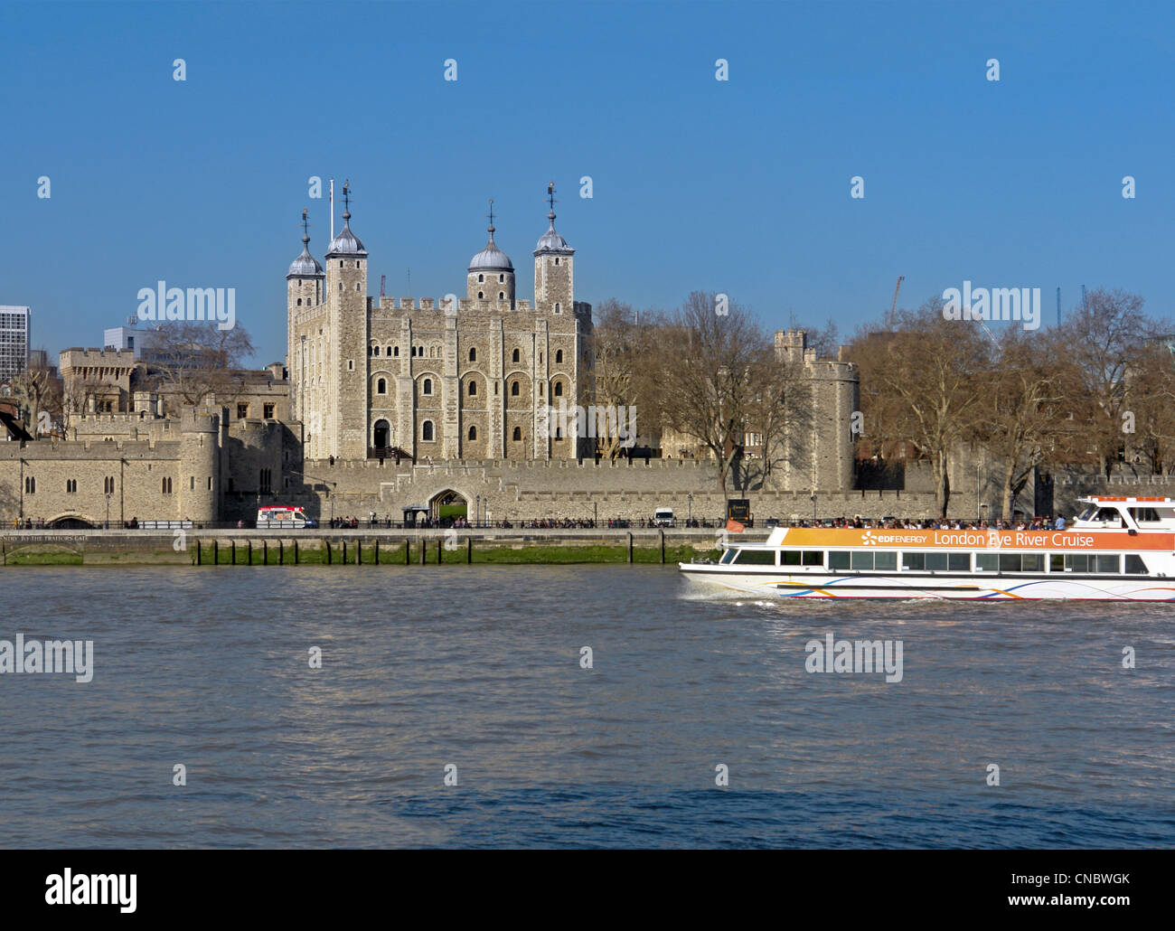 A Thames river cruise boat passing the Tower of London - Stock Image