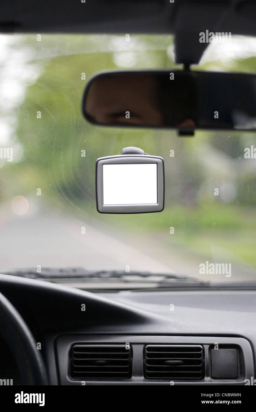 Driver using a portable gps unit that is mounted to the windshield. The blank screen includes clipping path. Stock Photo