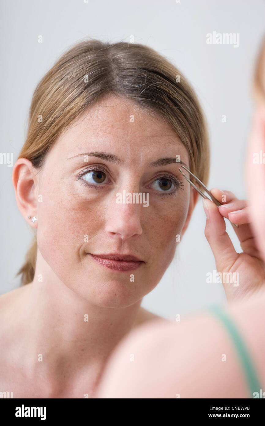 Woman tweezing her eyebrows - Stock Image