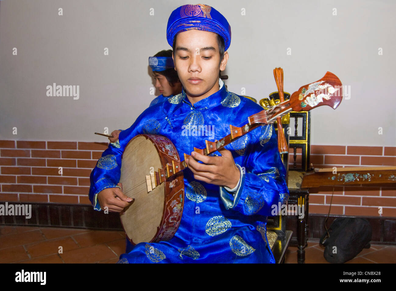 Horizontal close up view of traditional Vietnamese musician playing the dan nguyet or Full Moon lute guitar in costume. - Stock Image
