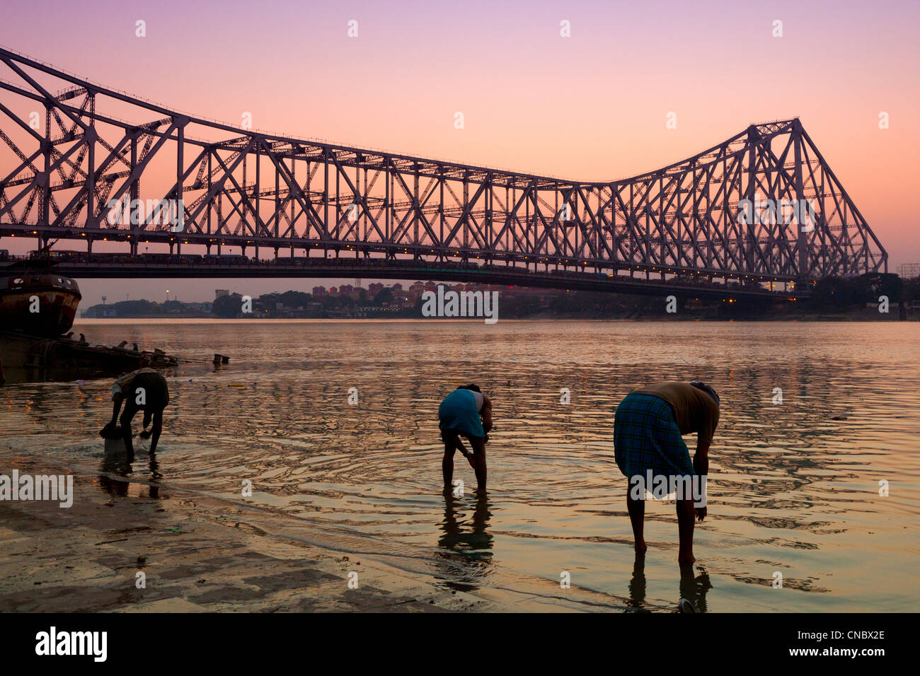 India, West Bengal, Kolkata (calcutta), family cleaning cooking utensils in the Hooghly river with Howrah suspension - Stock Image
