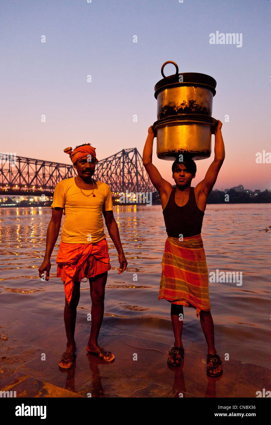 India, West Bengal, Kolkata (calcutta), two men with cooking utensils at Hooghly River with howrah suspension Bridge - Stock Image