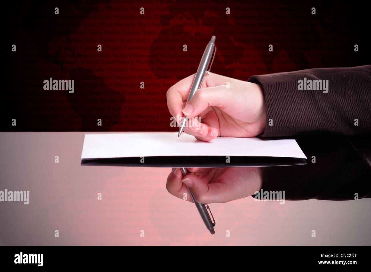 Businessperson writing a document with a world map behind - Stock Image
