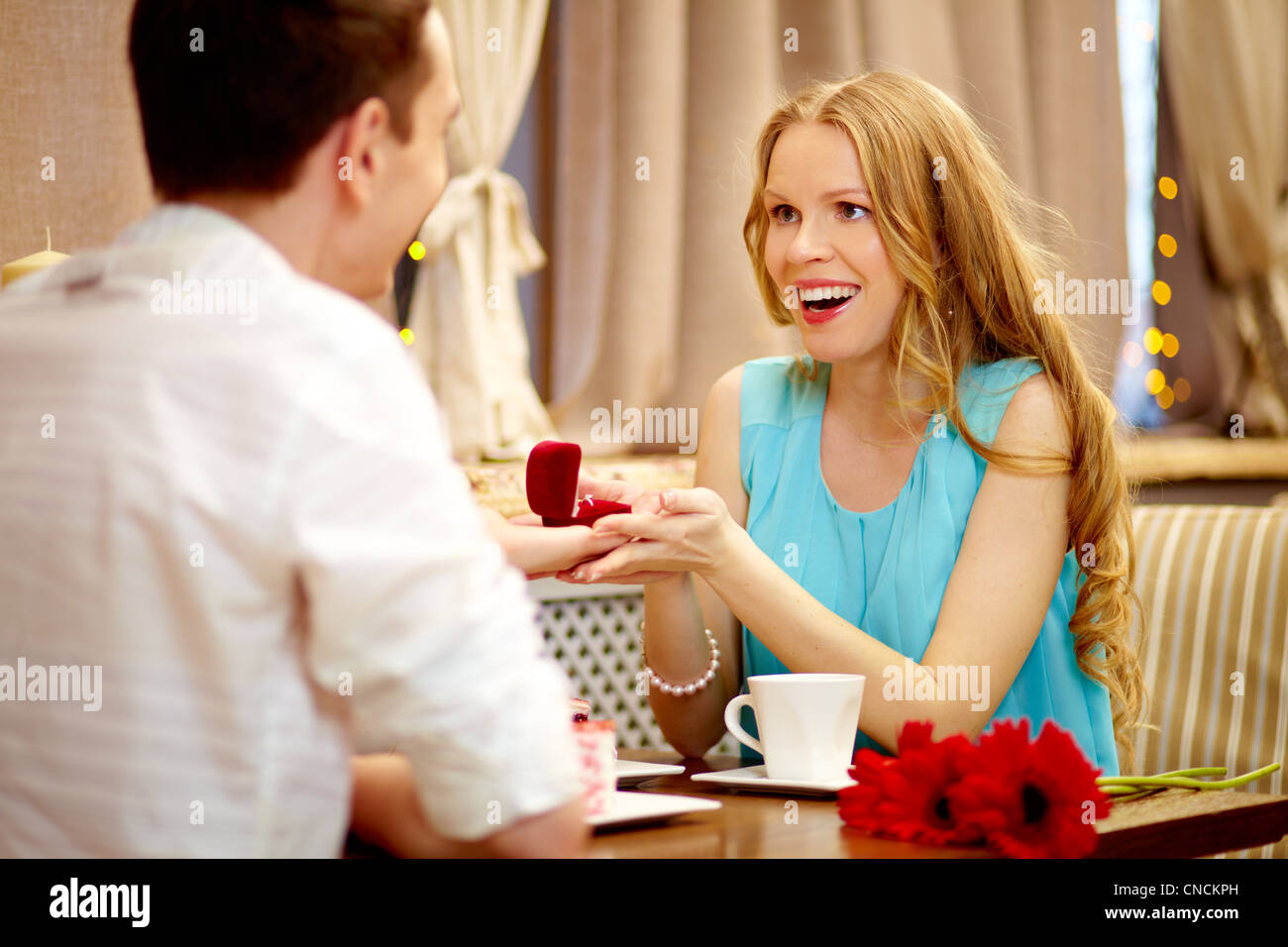Astonished woman looking at her boyfriend showing gift at lunch - Stock Image