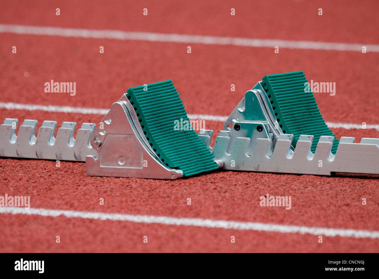 Starting blocks on a running track at the start of a  race - Stock Image