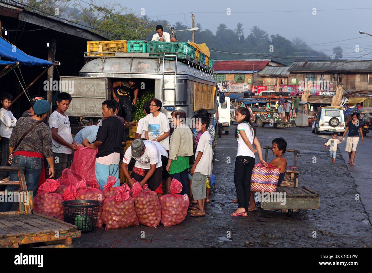 Limes being sold from a fully laden bus at the waterfont market. Tacloban, Leyte Island, Leyte, Eastern Visayas, - Stock Image