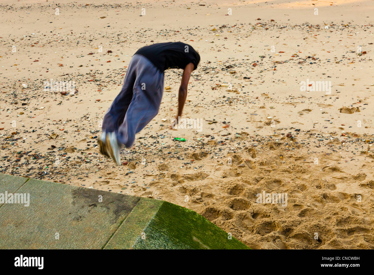Child somersaulting on to sand from a height, London, England, UK Stock Photo