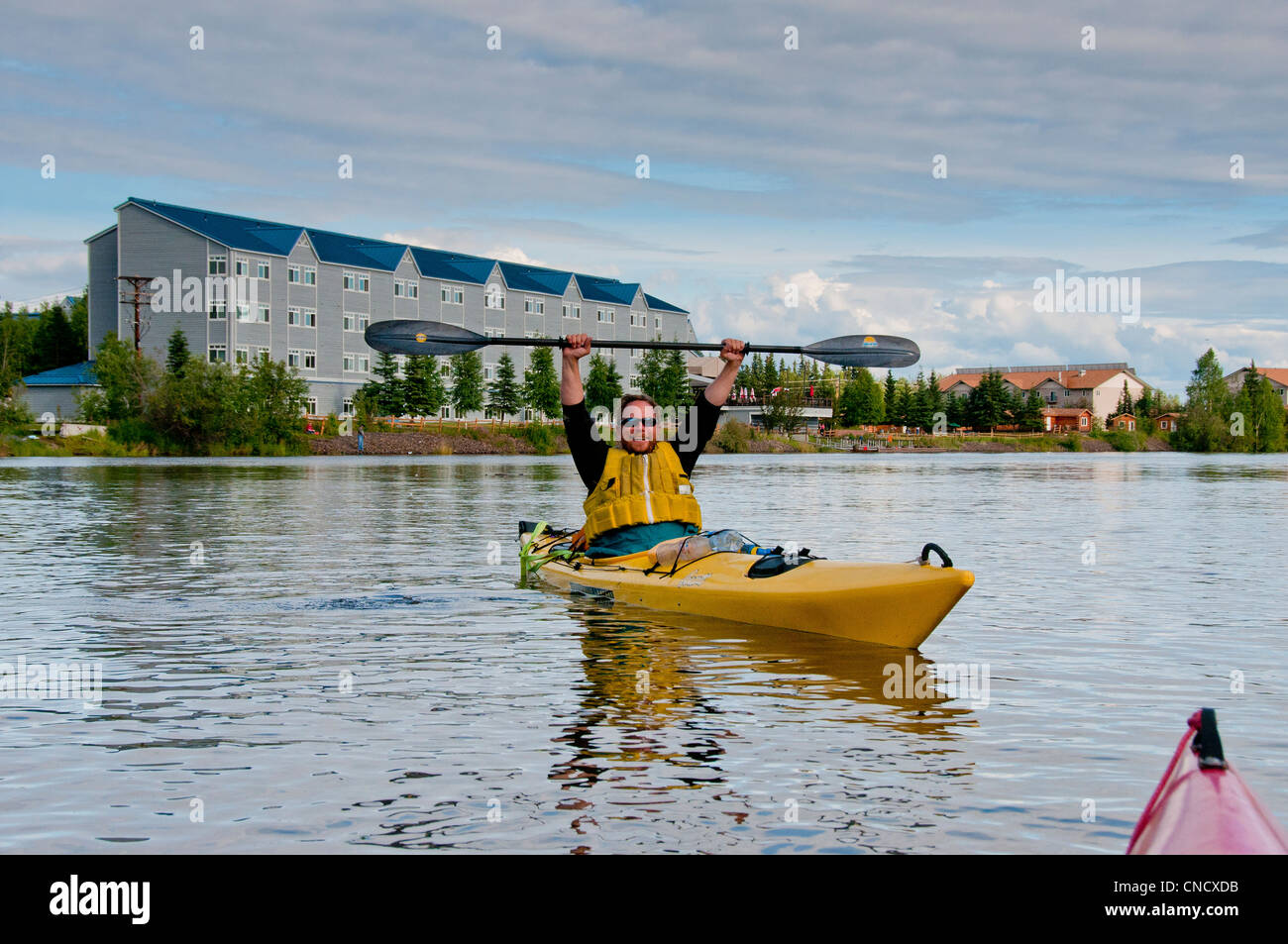 Man raises his arms in triumph after paddling the Chena River in Fairbanks,Interior Alaska, Summer - Stock Image