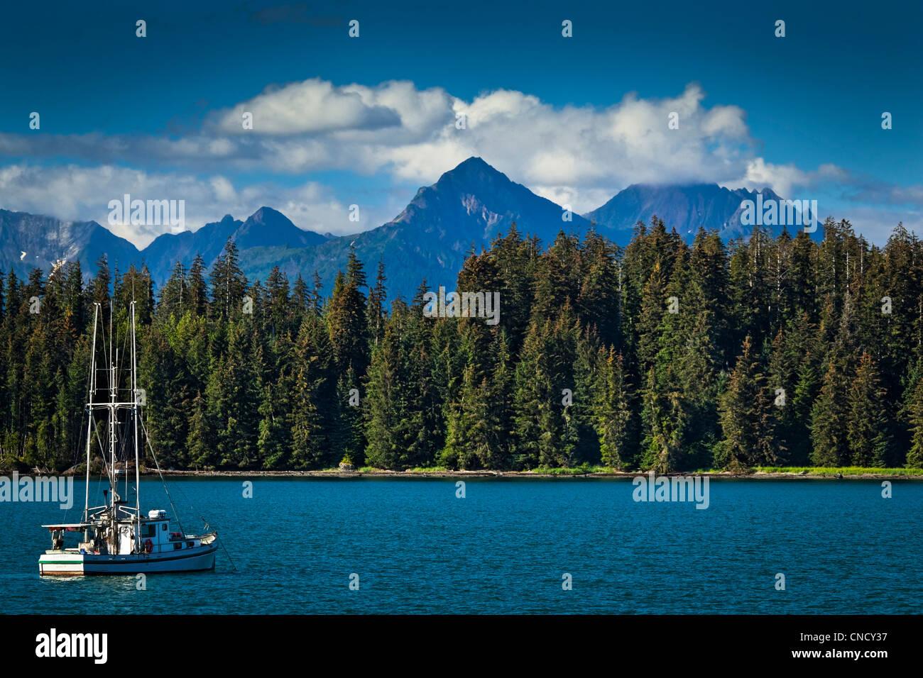 A sailboat anchored in Bartlett Cove, Glacier Bay National Park & Preserve, Southeast Alaska, Summer - Stock Image