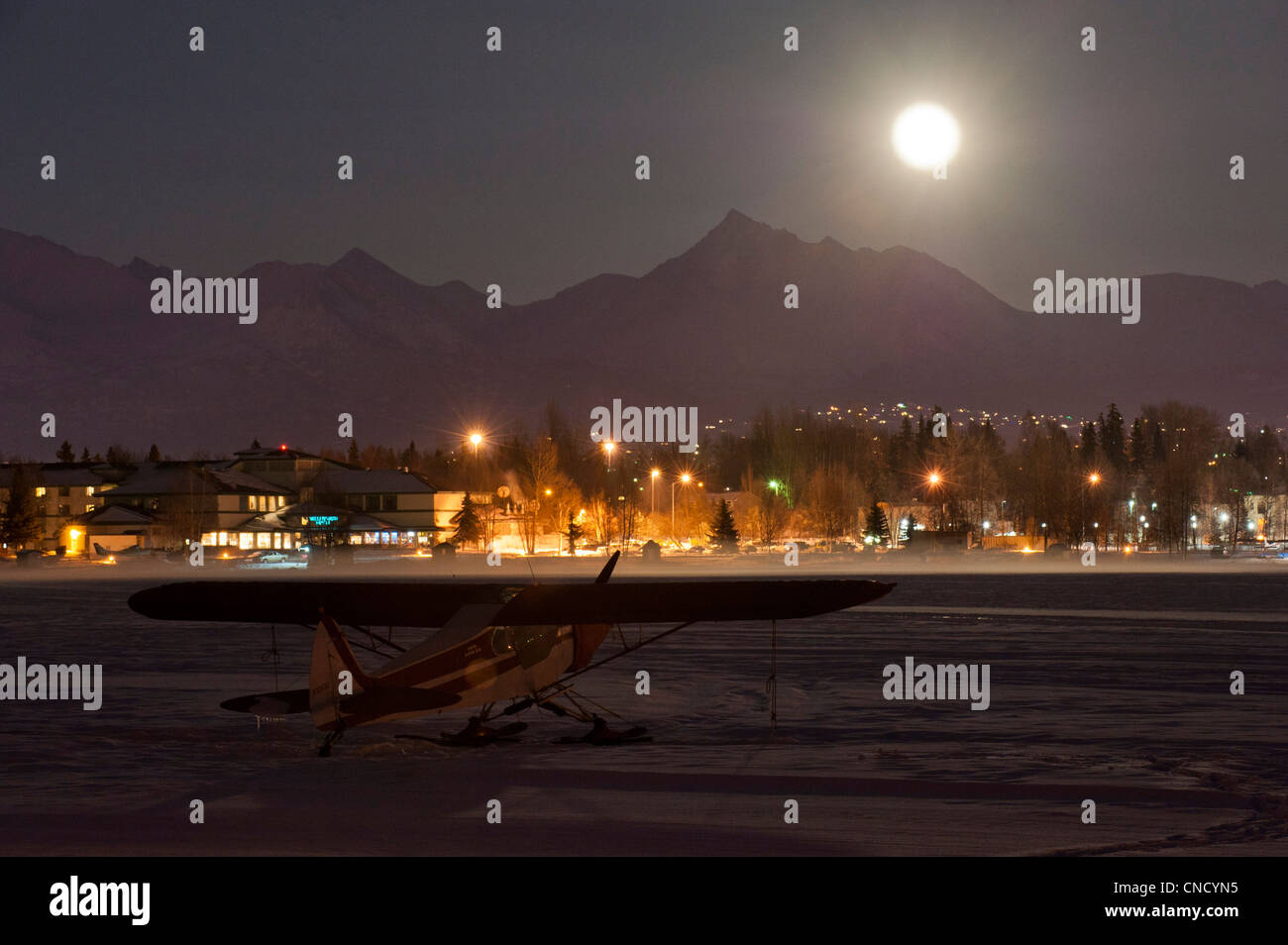 A full moon rises over the Chugach Mountains with a ski plane parked on the frozen Lake Hood in the foreground, Stock Photo