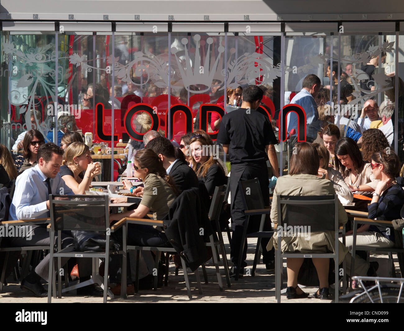 Many people enjoying the sun during their lunch break on Place du Luxembourg in Brussels, Belgium Stock Photo