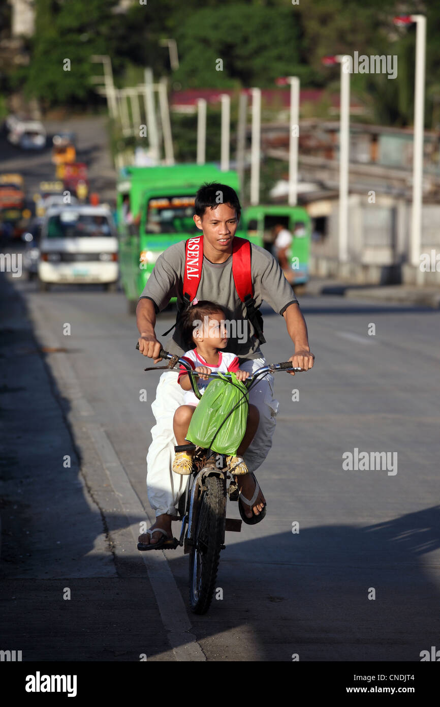 Father and daughter on bicycle. Tagbilaran, Bohol Island, Bohol, Central Visayas, Philippines, South-East Asia, - Stock Image