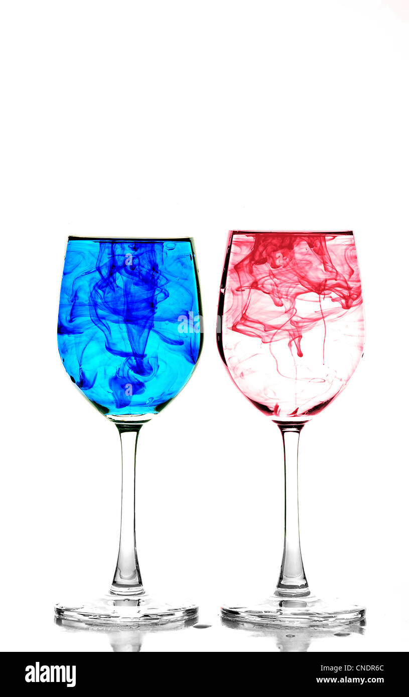 Two wine glasses filled with water and spreading red and blue ink - Stock Image
