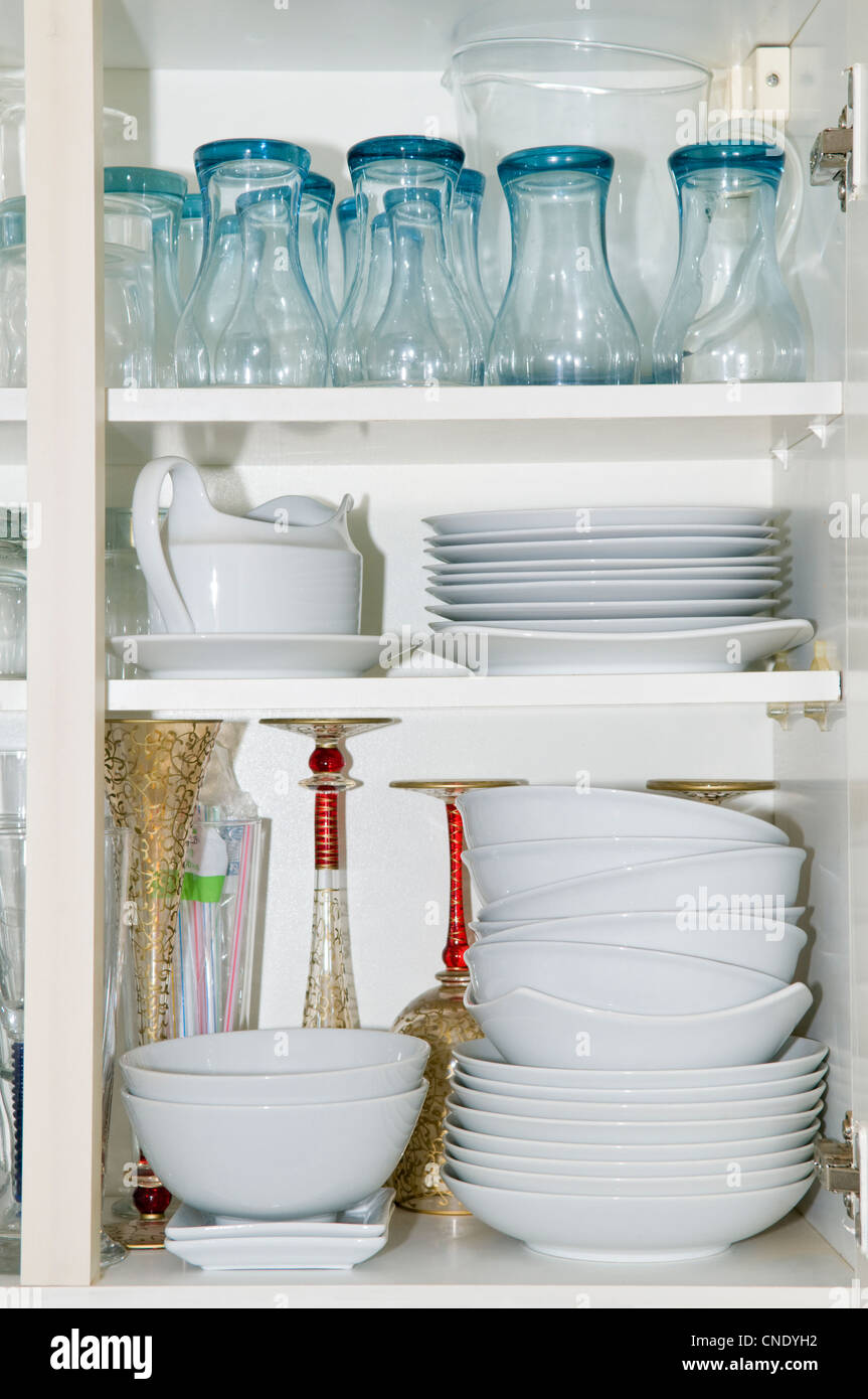 Kitchen cupboard contents showing crockery and glasses - Stock Image