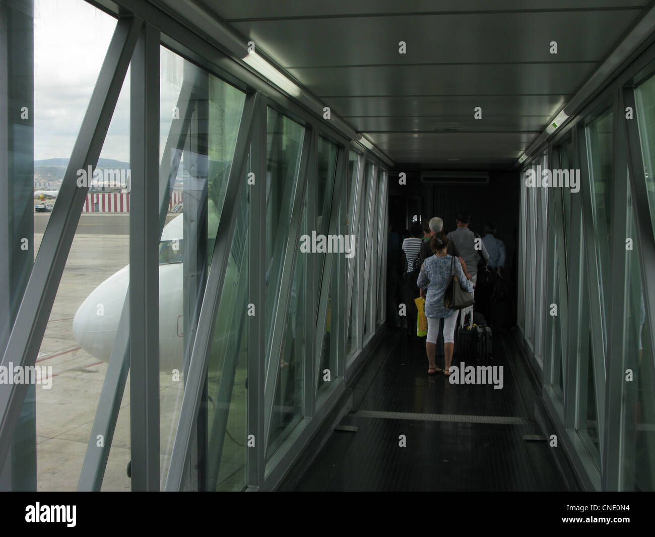 passengers boarding plane by finger dock - Stock Image