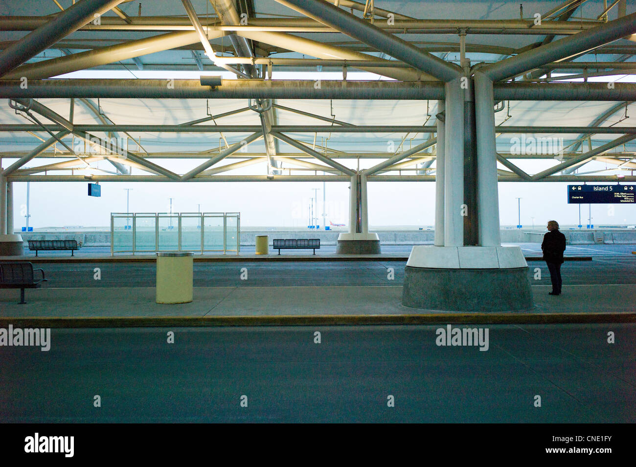 Lone woman waiting for a ride at the terminal at the Denver International Airport, Denver, Colorado, USA - Stock Image