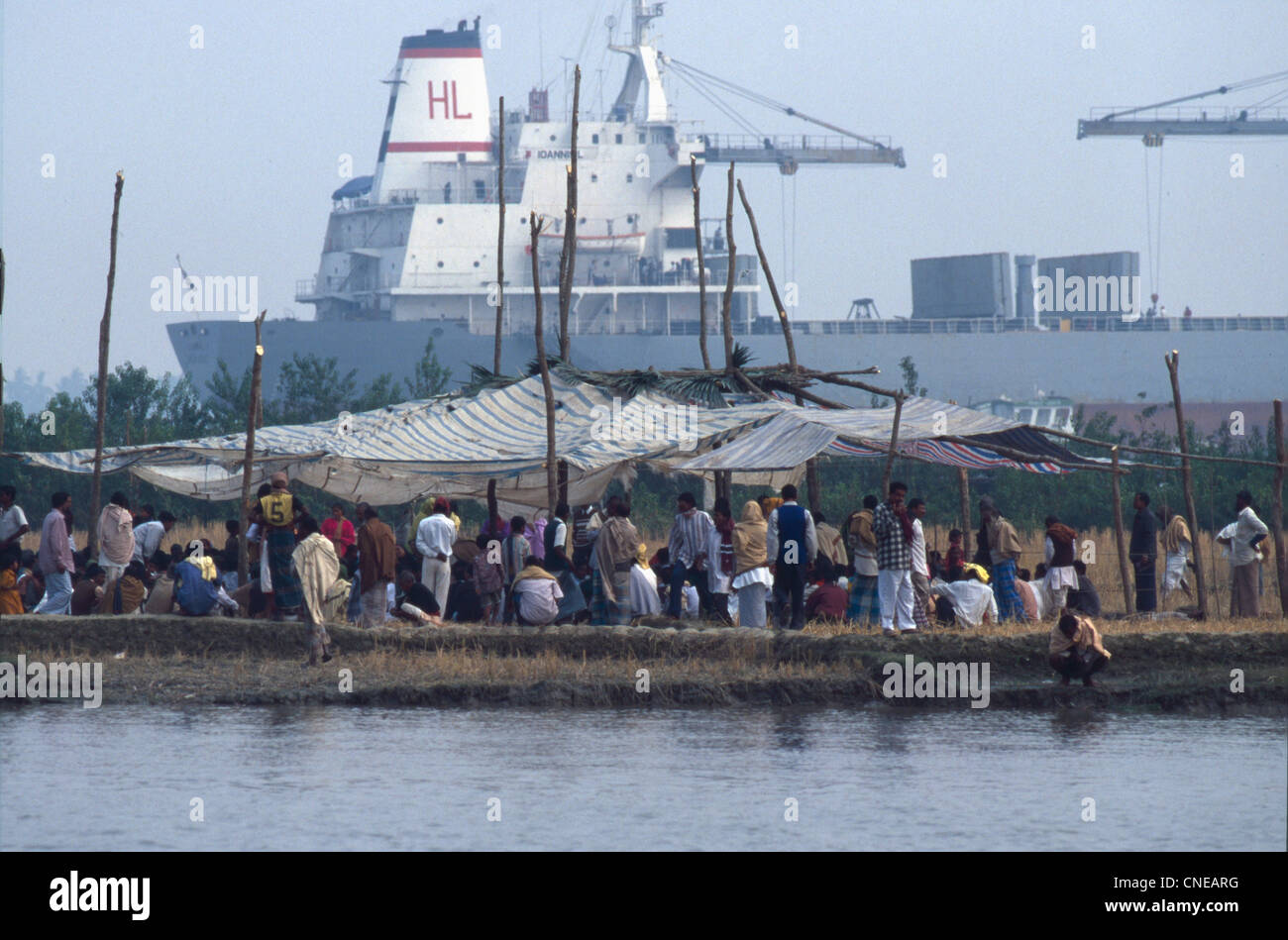 Dahka. A marketplace in the Buriganga river. (Ganges-Brahmaputra River Basin) and a big boat in the background - Stock Image