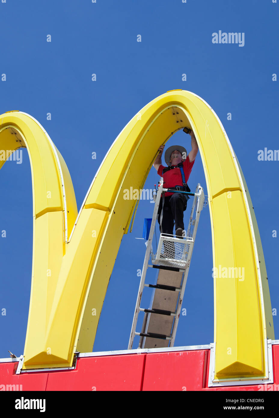 Detroit, Michigan - A worker repairs a McDonald's 'Golden Arches' sign. - Stock Image