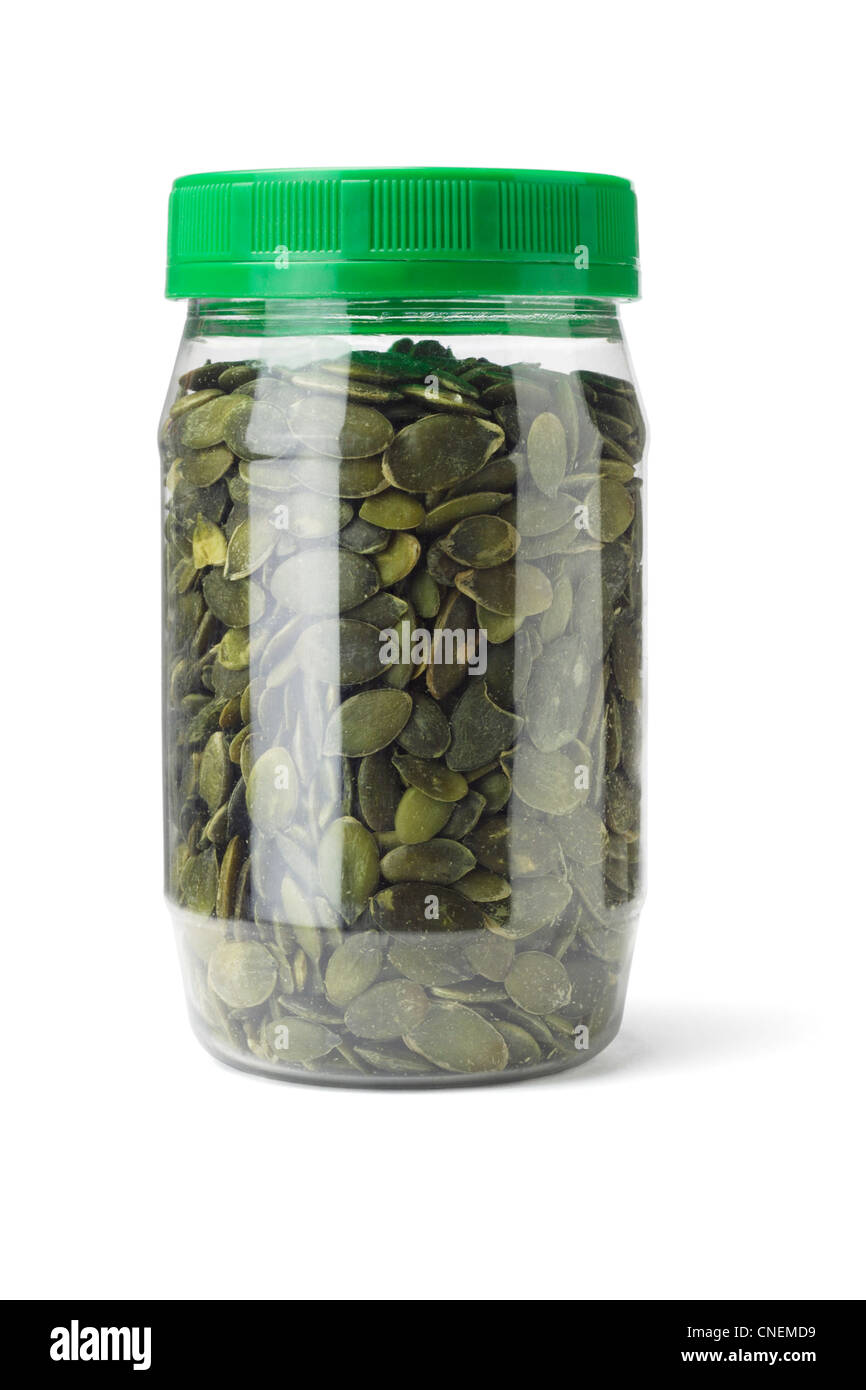 Dried Pumpkin Seeds in Plastic Bottle on White Background - Stock Image