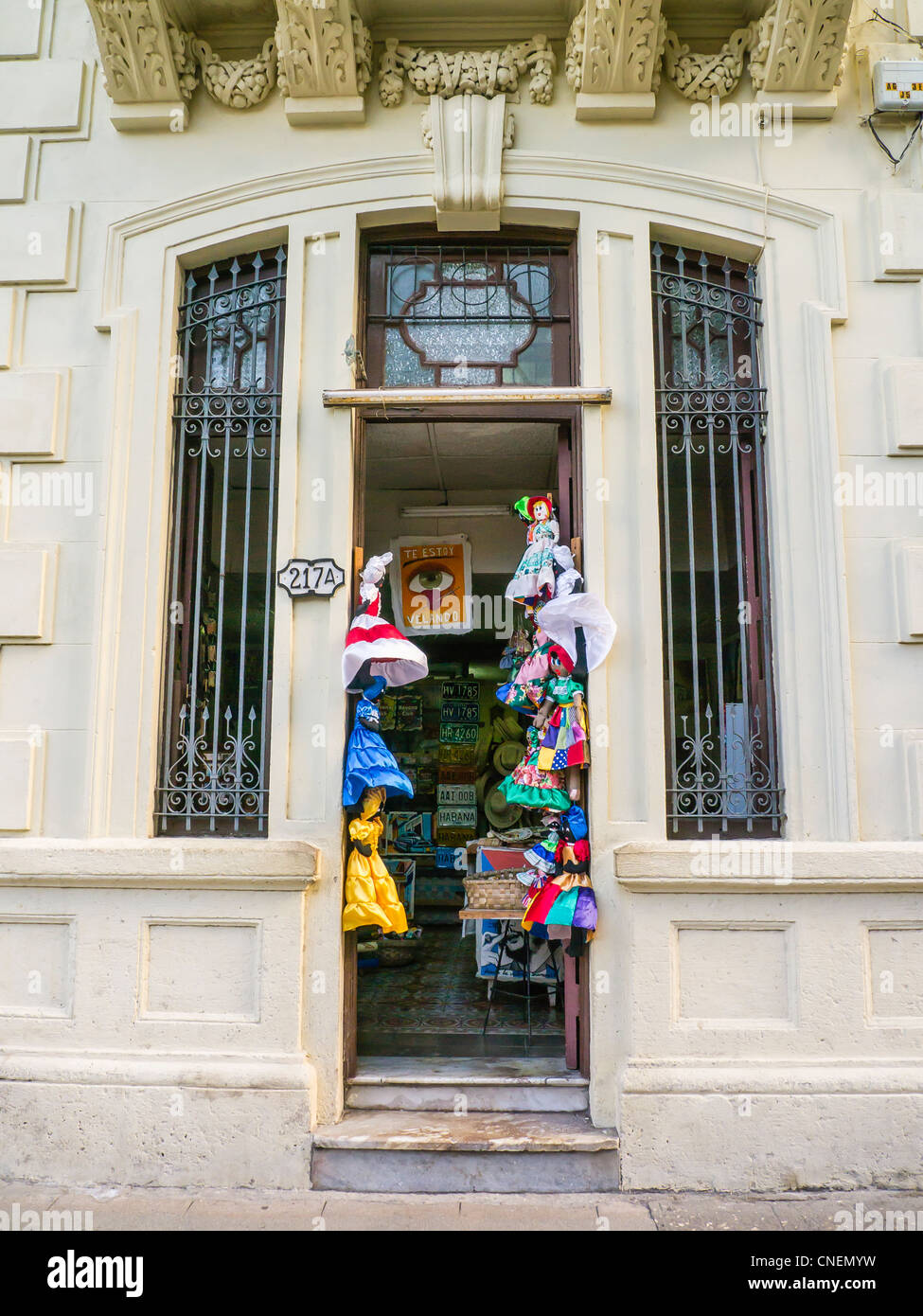 Children's clothing hangs on either side of the entrance door of a shop in Havana, Cuba. - Stock Image