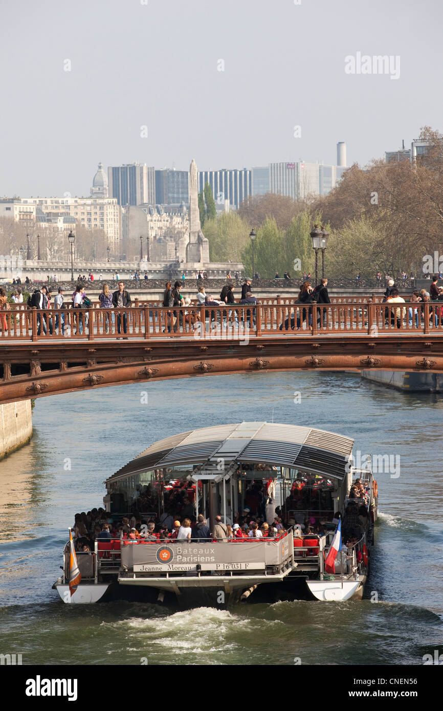 Tourist boat passes under Pont au Double, River Seine, Paris, France - Stock Image