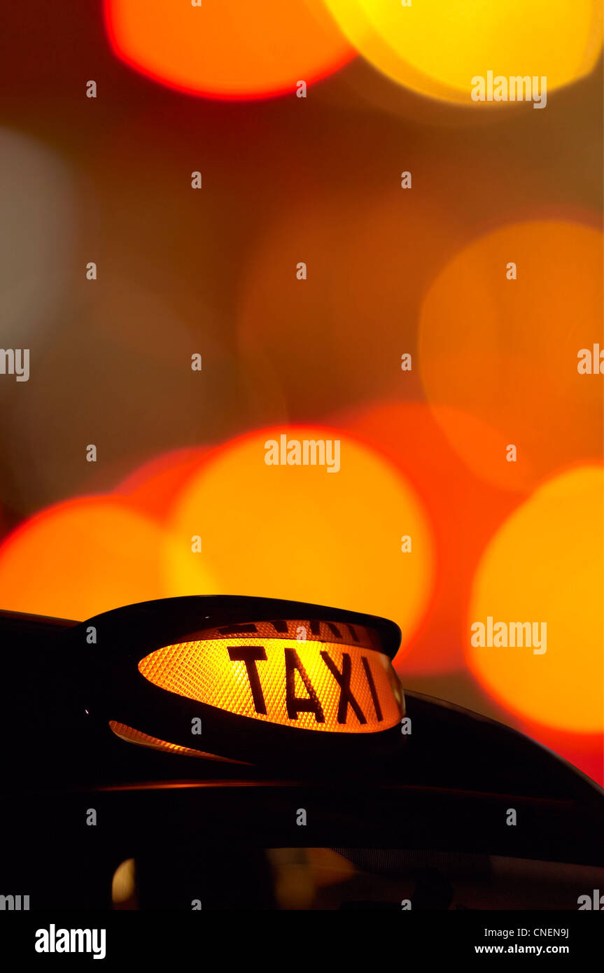 a lit london taxi sign at night with de-focussed lights in the background Stock Photo