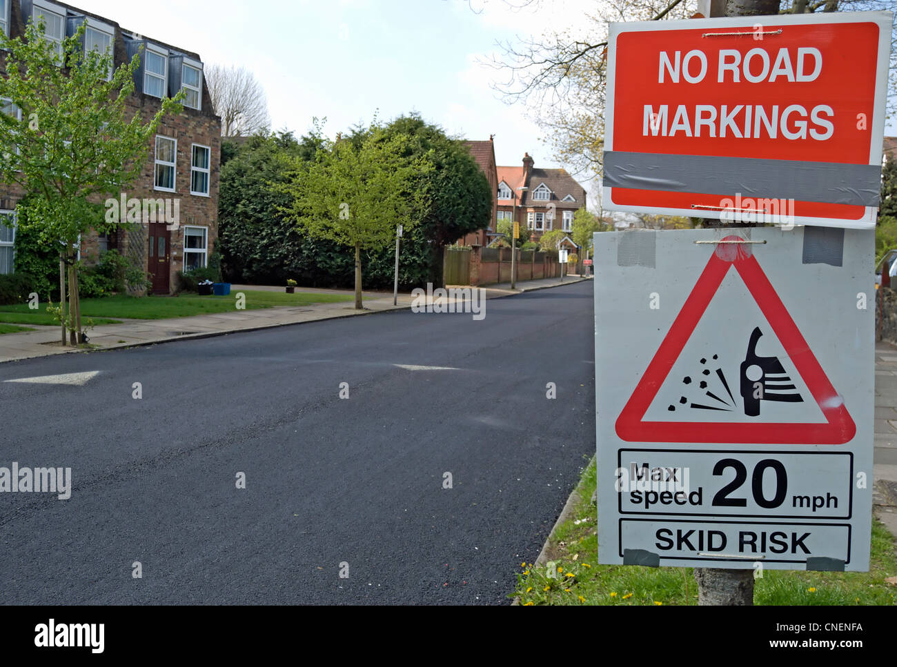 no road markings and 20mph speed limit loose chippings signs beside newly resurfaced road - Stock Image