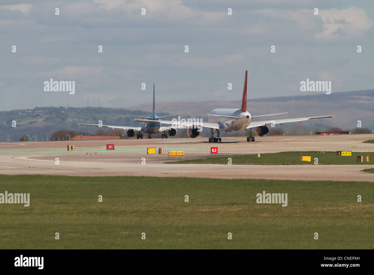 two jet airliners taxiing to the runway at Manchester airport - Stock Image