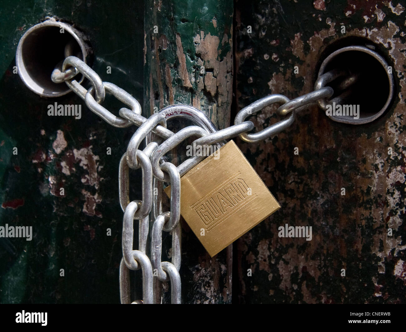 Padlock and chains on door house - Stock Image