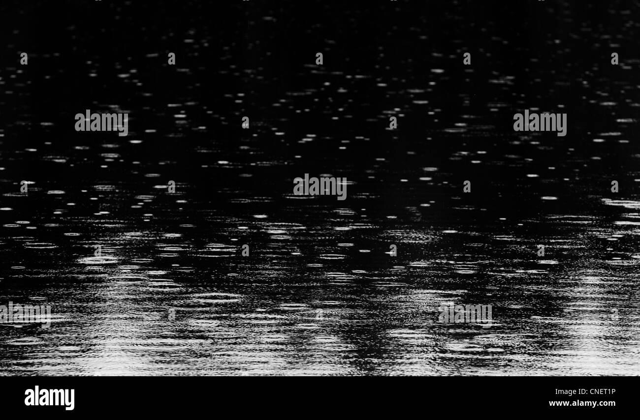 Raindrops falling to lake surface - Stock Image