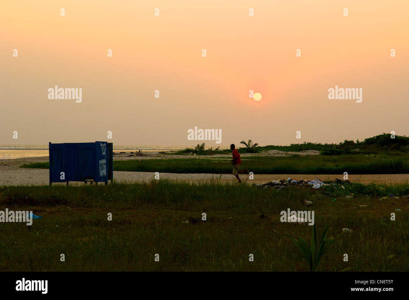 Man running at the beach in Eket in the oil-rich Niger Delta in Nigeria - Stock Image