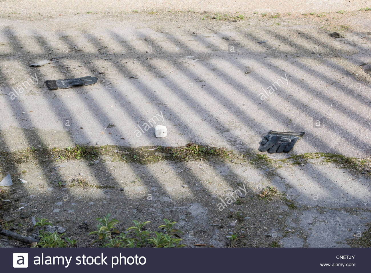 Shadow of a fence falls on derelict land with discarded gloves littering the ground - Stock Image