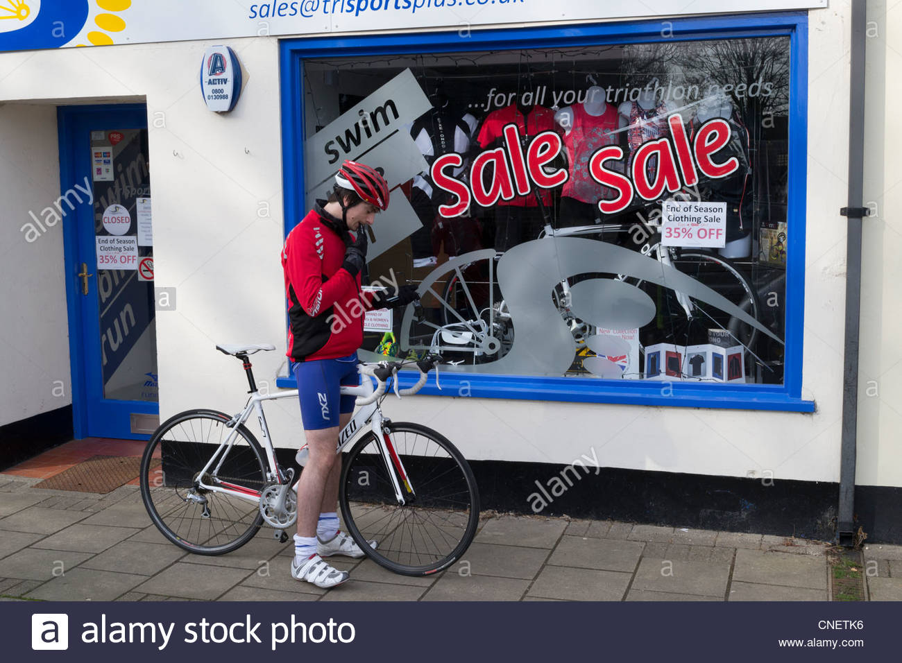Cyclist waits for Triathlon shop to open in Huntingdon High