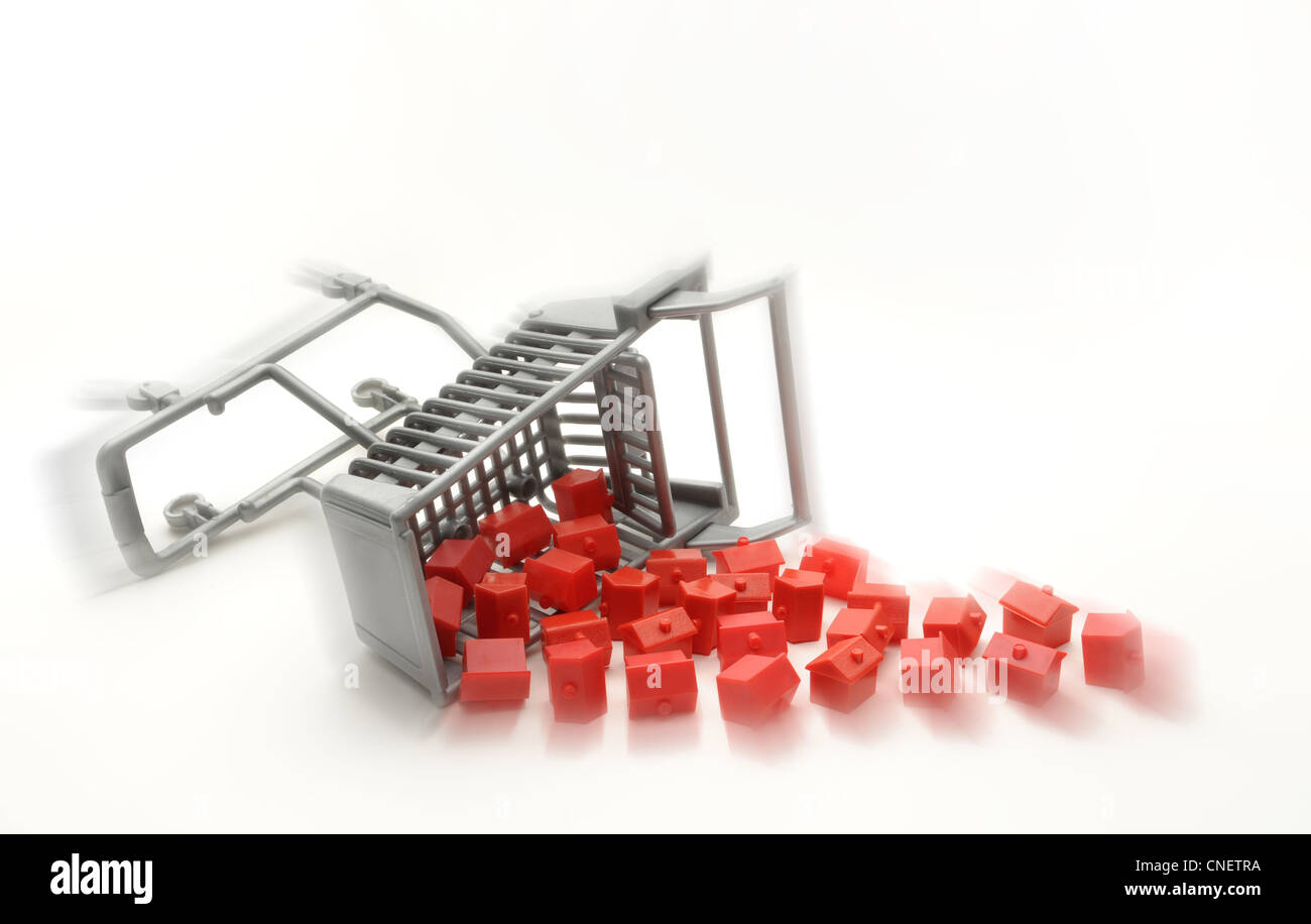 UPTURNED SUPERMARKET TROLLEY WITH MODEL HOUSES RE HOUSING MARKET PROPERTY HOME BUYERS PRICES HOMES MORTGAGES INCOMES - Stock Image