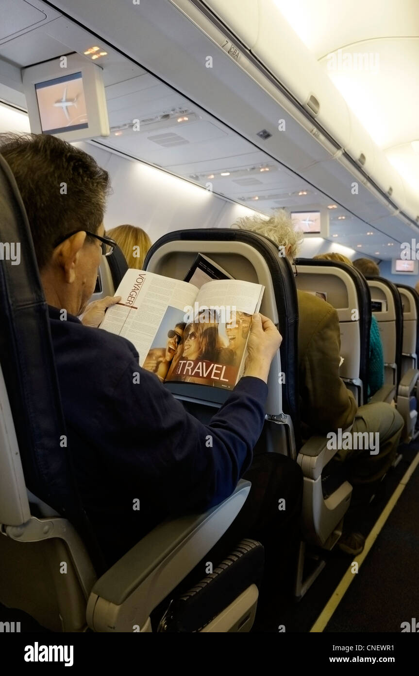 Man on an Airplane reading an Inflight Magazine - Stock Image