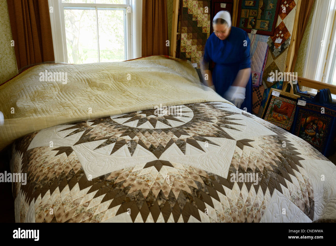 Mennonite seamstress displaying handmade quilts in her bedroom near St Jacobs Ontario - Stock Image