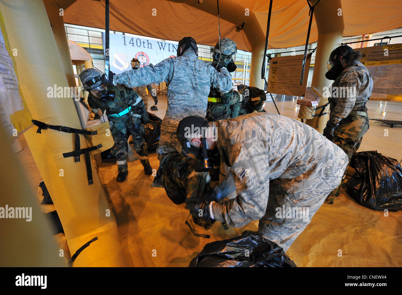 Members of the 140th Wing, help each other remove their Chemical Protective Overgarment while processing through - Stock Image