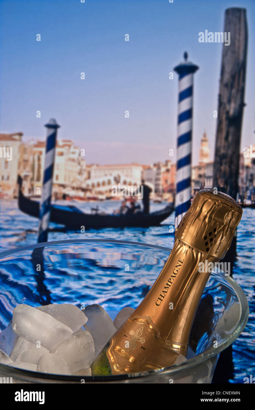 Concept / Bottle of champagne on ice with Venetian gondola and Rialto Bridge behind. Venice Italy - Stock Image