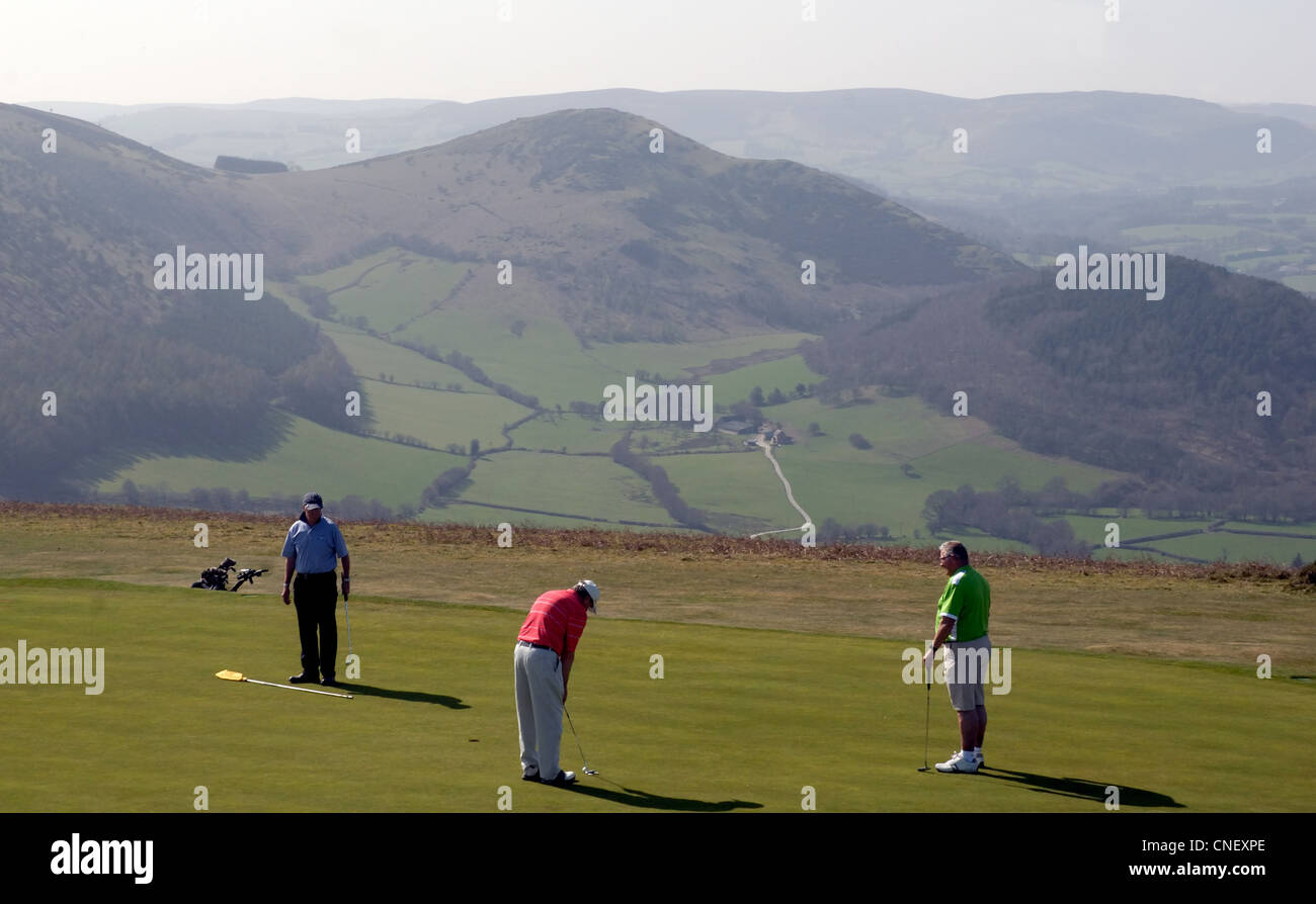 Three golfers play golf on the ninth hole at Kington Golg Club on Bradnor Hill Kington. I - Stock Image